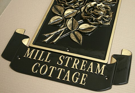 Cast metal sign in black and gold