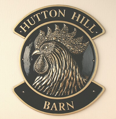 Sculptured house sign with rooster in black and gold