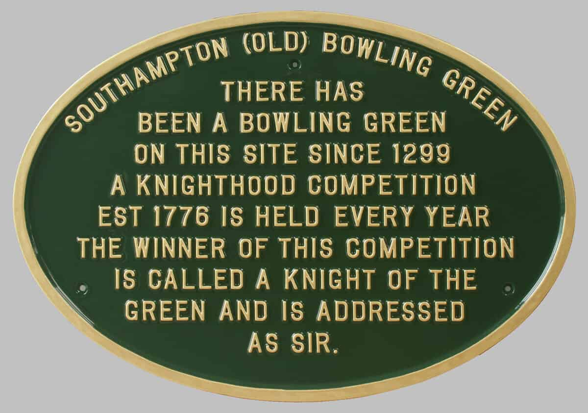 Large oval commemorative plaque in dark green and gold