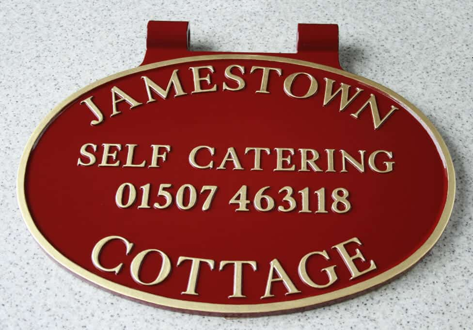 Cast aluminium oval swinging sign in maroon and gold