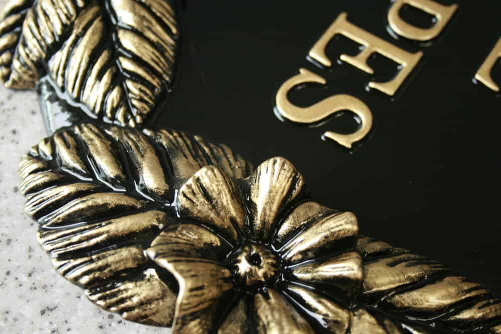 House sign with flower design in black and gold