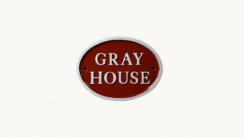 Small oval cast metal house sign in red and silver