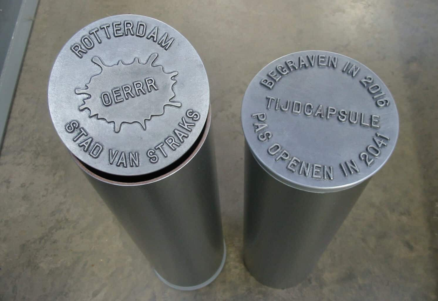 Two small composite time capsules with logo