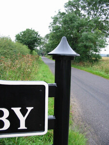 Black steel village sign frame with cast finial on english country lane