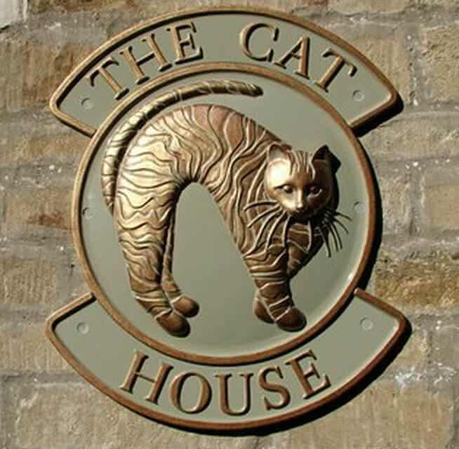 Cat house sign cast in metal with name top and bottom