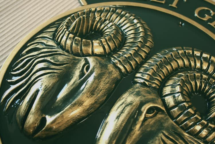 Cast metal rams heads in green and gold
