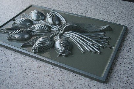 Cast metal wall sculpture in raised relief