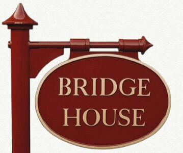 Double sided cast metal house sign in maroon and gold