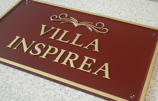 Traditional cast metal house sign in maroon and gold