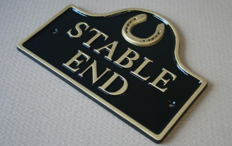 Arched top stable house sign with horseshoe motif in black and gold